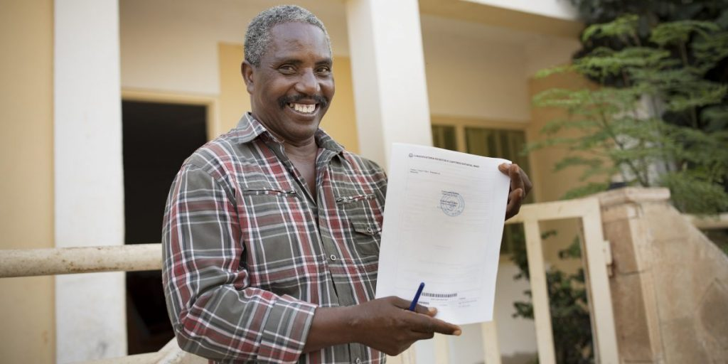 Manuel Gomes holds his newly acquired land title outside his home on the island of Maio, Cabo Verde. Mr. Gomes was able to obtain his title as a result of investments made as part of the MCC-Cabo Verde Compact that helped clarify land rights across the island nation. (Photo credit: Jake Lyell for MCC)