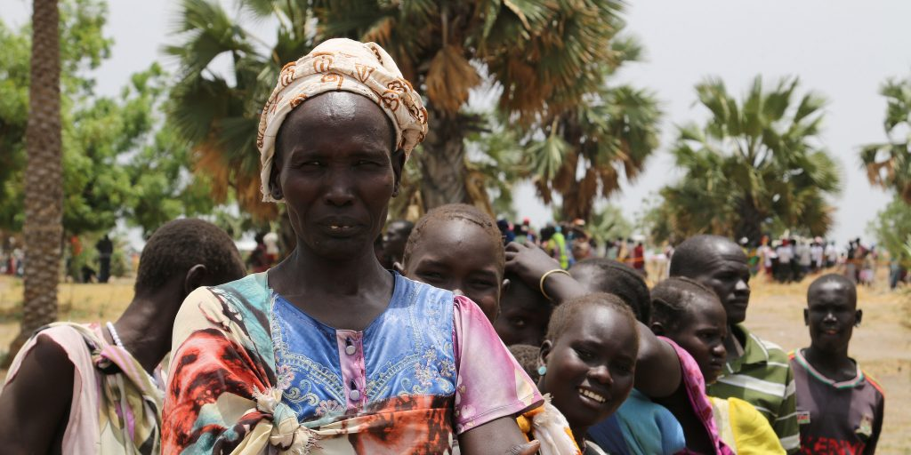 A woman waits at a temporary food distribution site in Leer, South Sudan. (Photo credit: Robert Oxley/DFID)