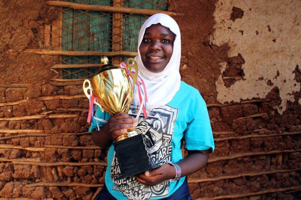 Die Schülerin Khadija hält stolz ihren Pokal