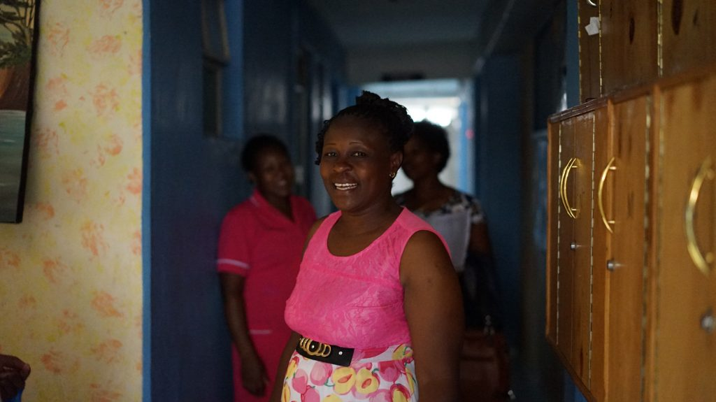 Lydiah in the hallway of St. George's where she has worked for four years with two nurses in the background.