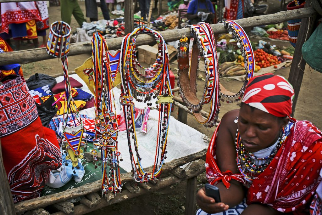 A Maasai woman checks her phone as she sells jewelry at the market in the town of Susua, Kenya, Wednesday, August 12, 2015. Many people in Africa don't have access to power in their homes and will walk many miles to charge their cell phones. In Kenya people almost can't live without their mobiles, they use it to pay for most things and connect with the world -- they use their mobiles instead of physical money, which is a lot safer and more practical. In nearly every location globally, at every demographic level, people possess some form of cell phone in todayÕs hyper connected world. Be it an iPhone or the simplest Nokia, the anxiety born of a fading battery has emerged as a common human experience. In villages, slums and any poorer area of Africa, charging stations have become the central social circles. The consequences of lost connections are palatable in Kenya, and the opportunities and growth that come with access to reliable power is transformative. (Photo credit/Tara Todras-Whitehill)