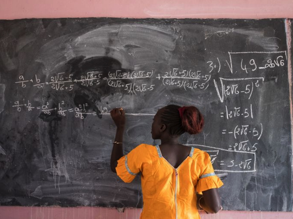 Safi Mballo, 18, writes on school blackboard at Sikilos School in Kolda region, Senegal. Safi walks 7km to school and back each day.