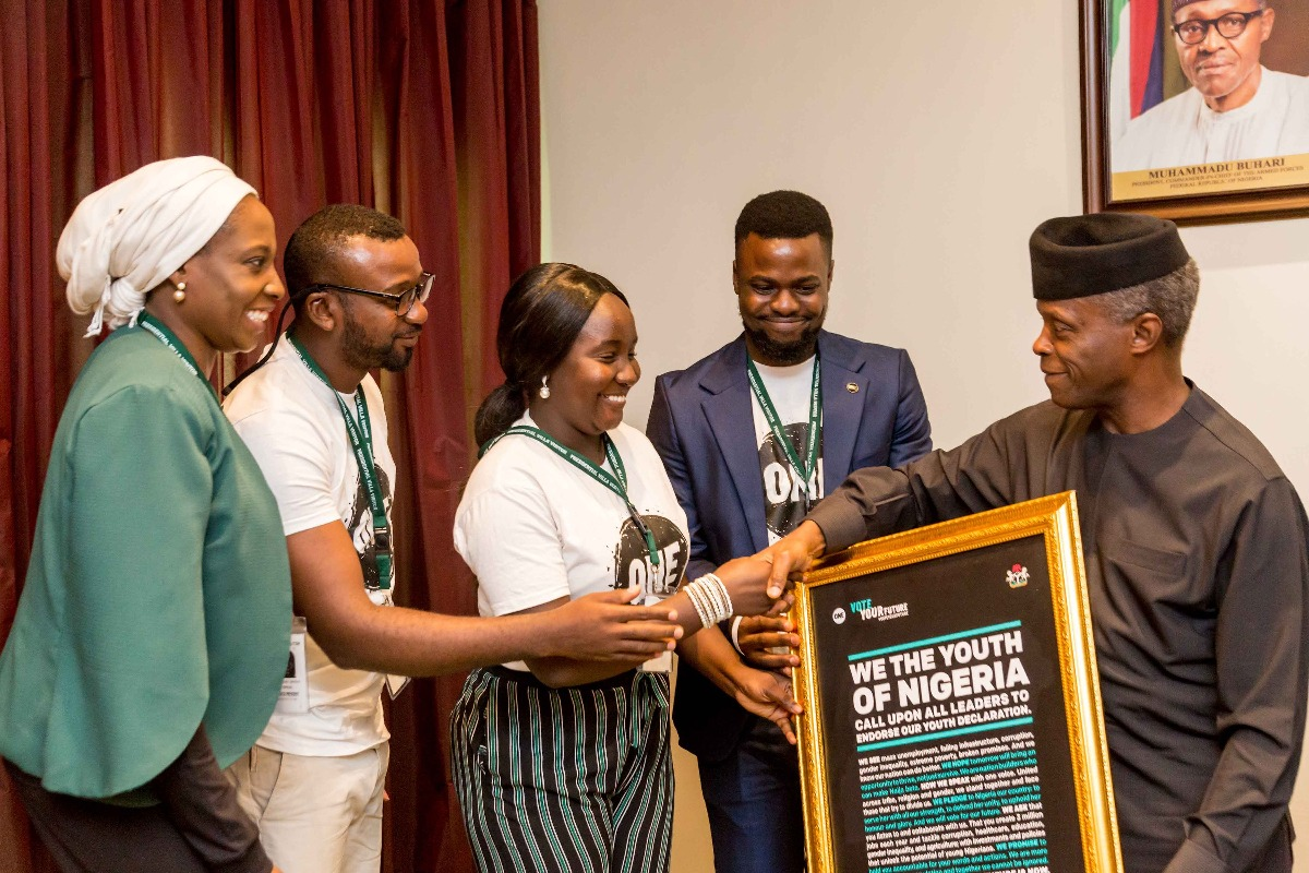 Wadi Ben-Hirki (middle) a ONE member, hands the Youth Declaration to Vice President of Nigeria, Prof. Yemi Osinbajo (right).