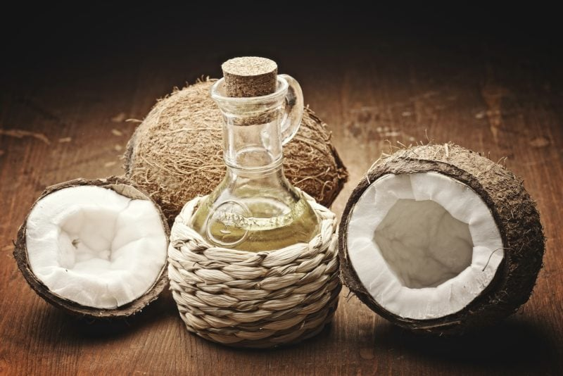 coconut oil and coconuts on wooden background