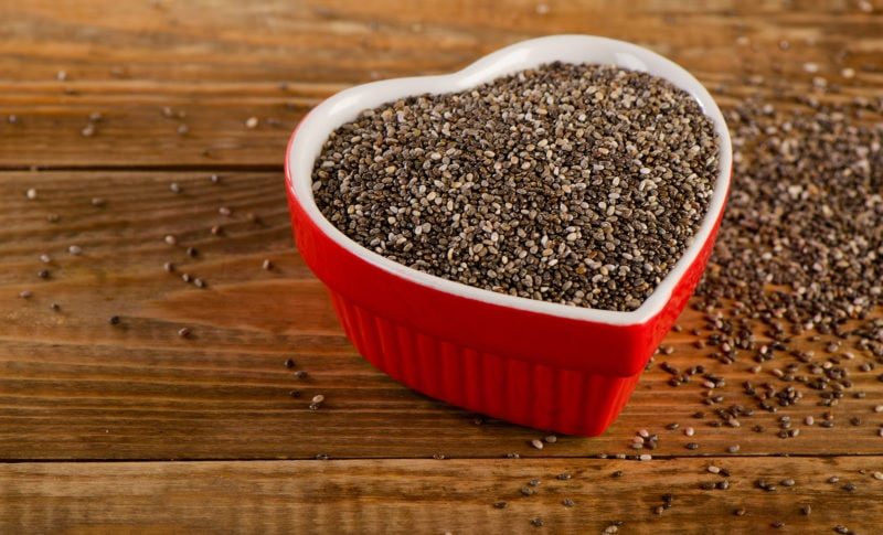 chia seeds in red heart-shaped bowl on wooden background