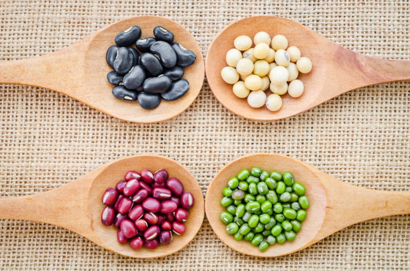 collection of various types of beans in wooden spoons