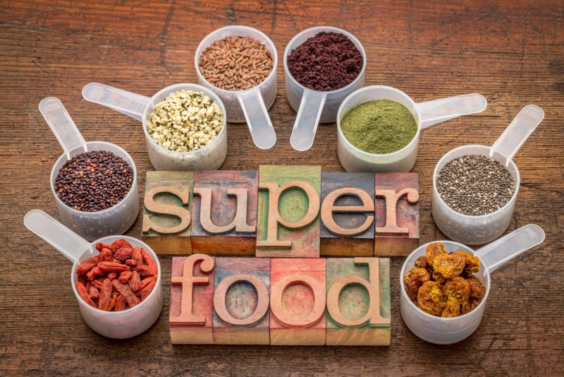 various superfoods on wooden table