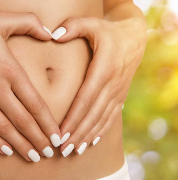 Body care pregnancy or diet concept female hands forming heart shape on the stomach