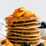 These healthy & fluffy vegan buckwheat pancakes are very easy to make. Only 4 ingredients, no eggs, dairy-free and gluten-free, these are topped with caramelized banana slices, blueberries, a peanut butter caramel coulis, walnuts and maple syrup for a sweet & savory breakfast. | onecleverchef.com #onecleverchef #breakfast #vegan #glutenfree