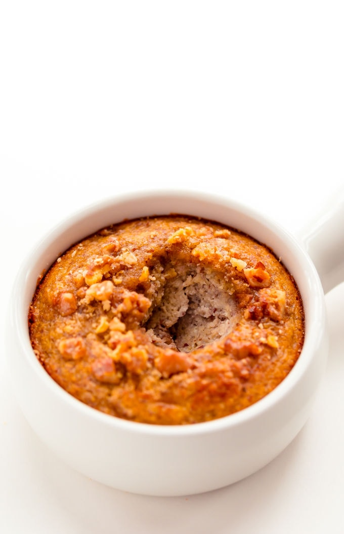Banana nut cake in a mug with a large bite missing on top.
