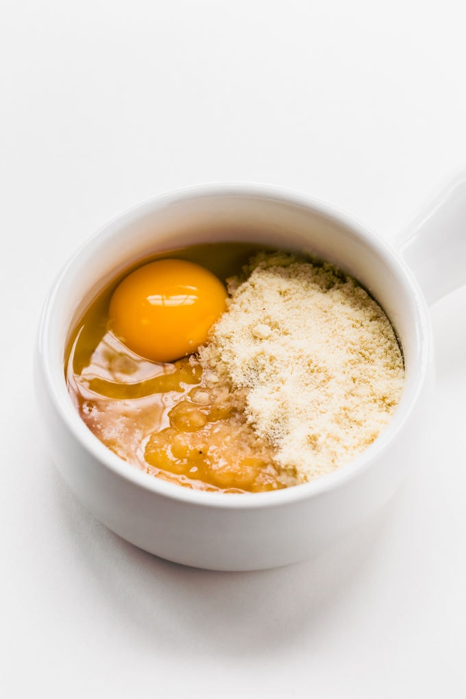 An egg, blanched almond flour and mashed banana in a mug.
