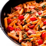 Red pesto penne pasta with chicken, spinach, baby tomatoes and onions in a large skillet.