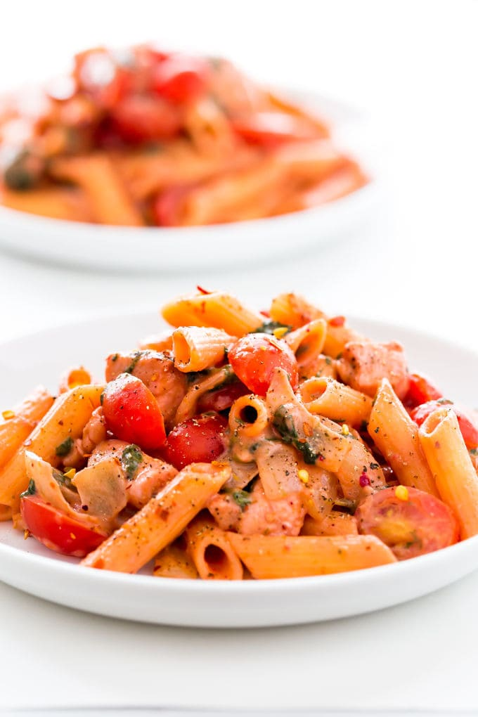 Red pesto penne pasta with chicken served in white plates.