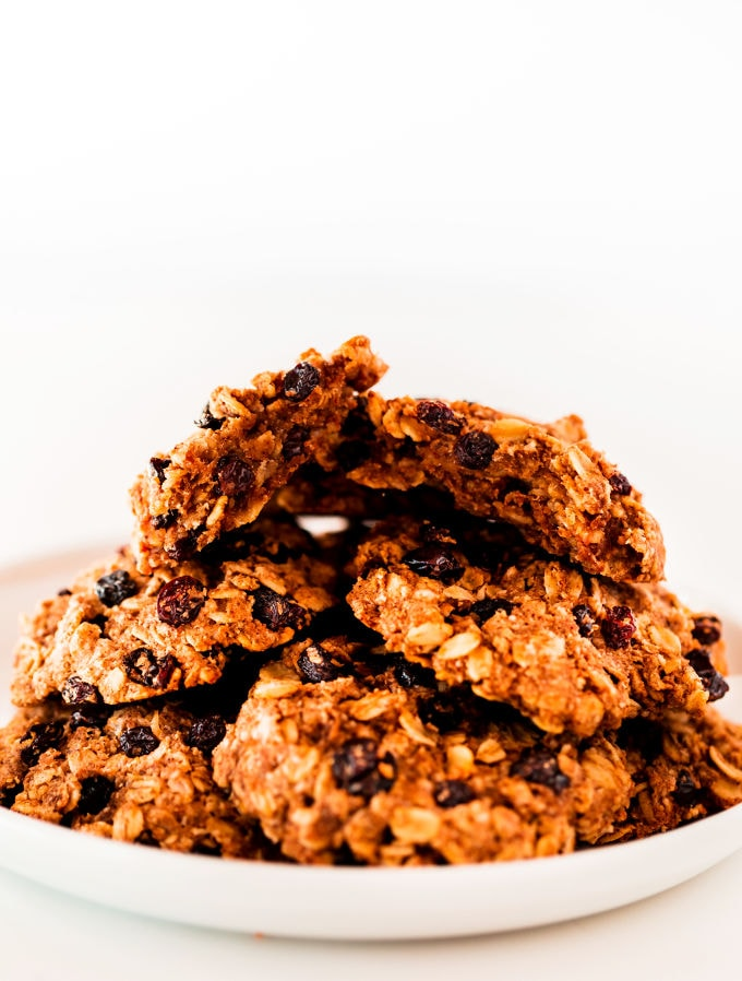 Oatmeal raisin cookies piled up on a white plate.