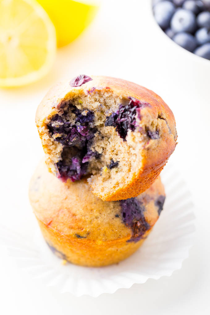 Two blueberry protein muffins stacked. The top one has a bite taken out of it.