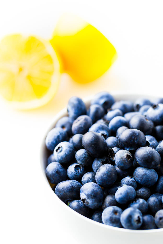 Blueberries and a lemon cut in half on a white background