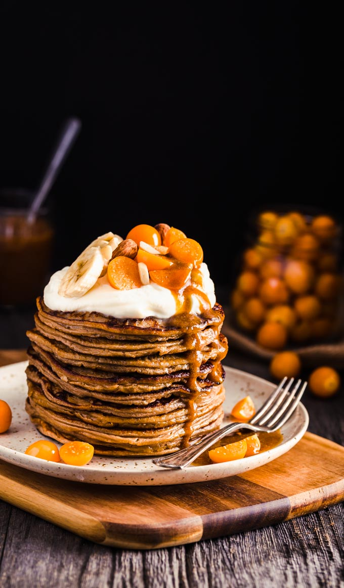A stack of pancakes with whipped cream and fruits on top.