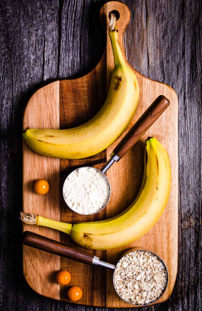 Bananas, oatmeal and vanilla protein powder on a wooden plank.