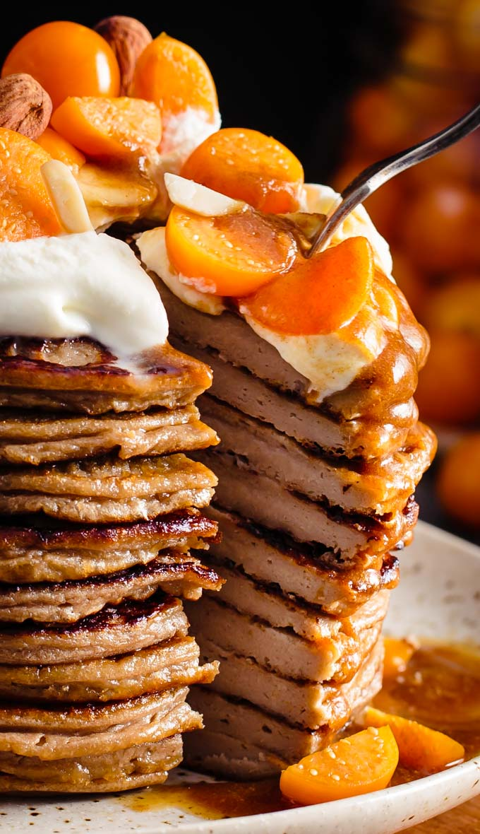 A stack of pancakes with whipped cream and fruits on top. A triangle slice is cut out of the stack and pulled out a bit.