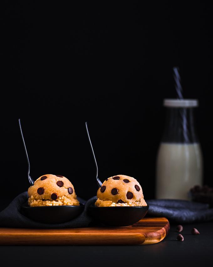 2 Edible cookie dough balls on a wooden board.