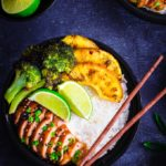 A bowl containing rice, teriyaki chicken, pineapple slices and broccoli florets.