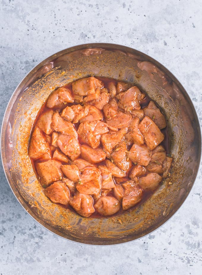 Chicken marinating in a large stainless bowl