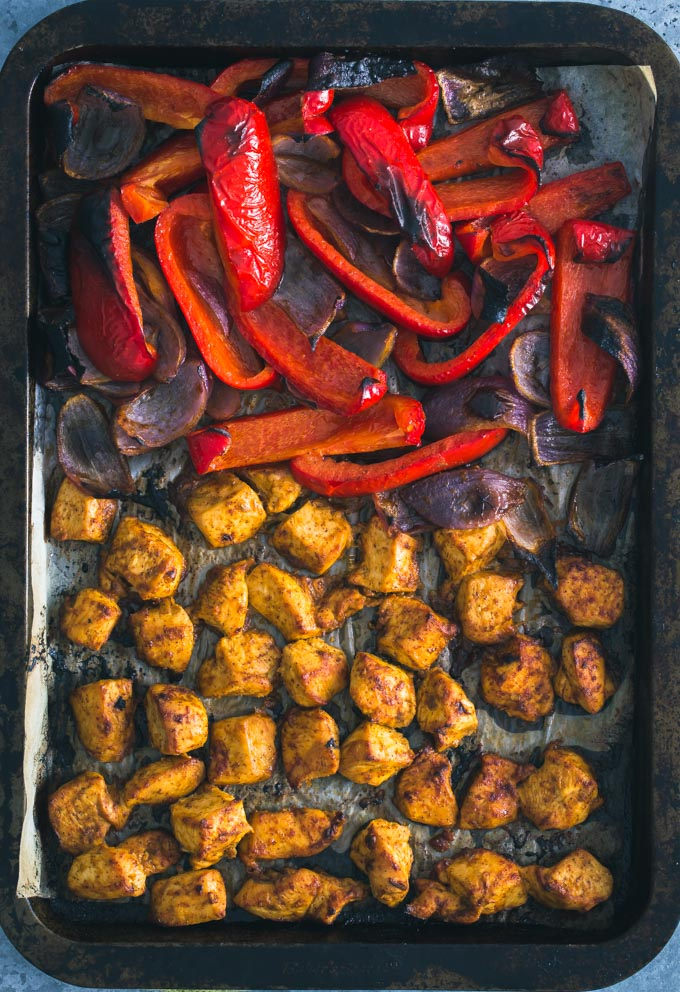 Chicken cubes, onion and bell pepper slices roasted in a pan.