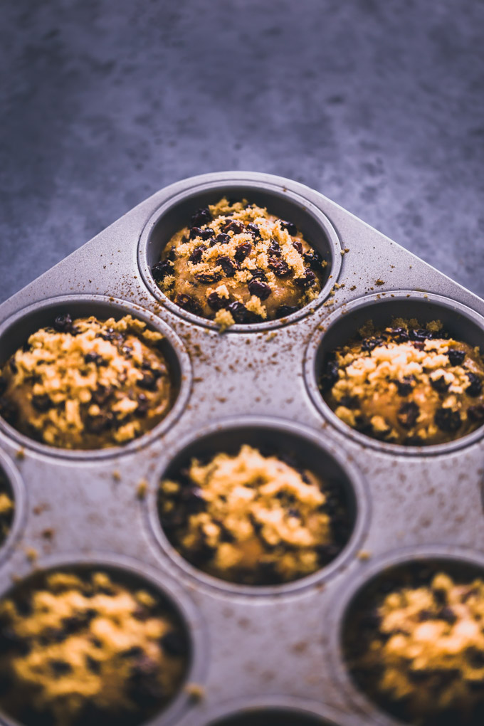 Oatmeal raisin protein muffin batter in a muffin tin