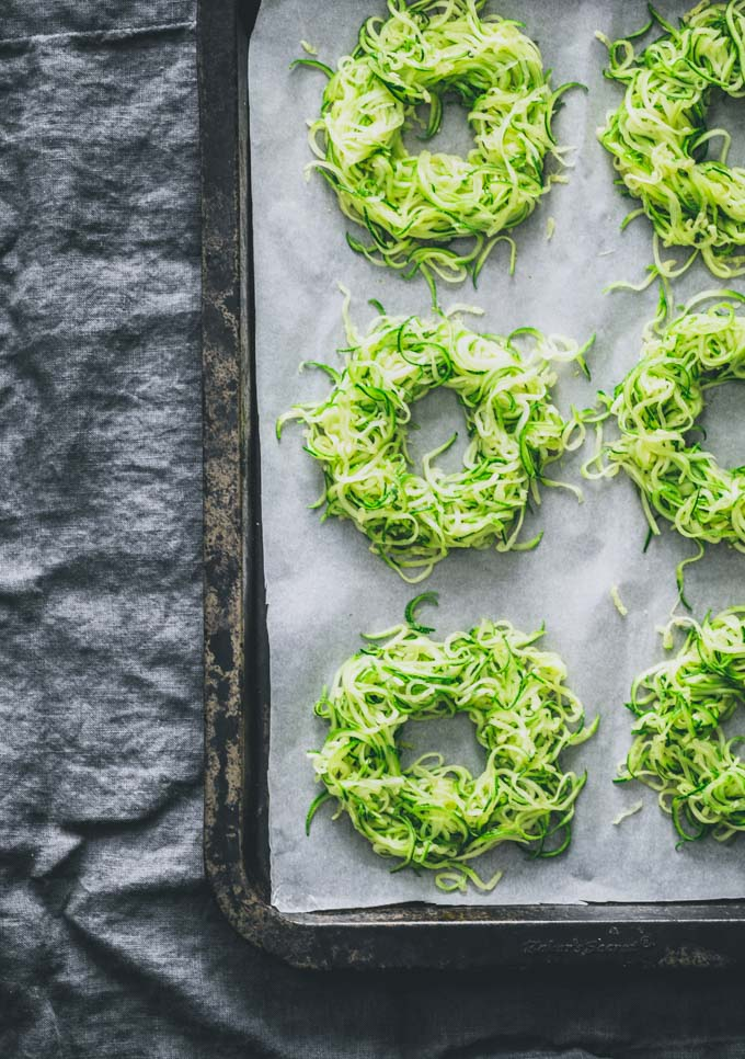 Zucchini egg nests on a sheet pan without the eggs