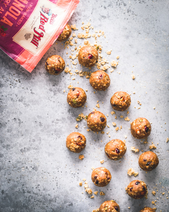 Cranberry Almond Granola Protein Balls on a blue background with a bobs red mill pan-baked granola bag