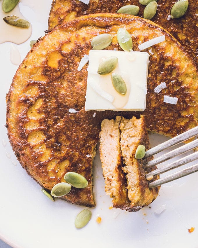 Two bites of Pumpkin Protein Pancakes planted on a fork