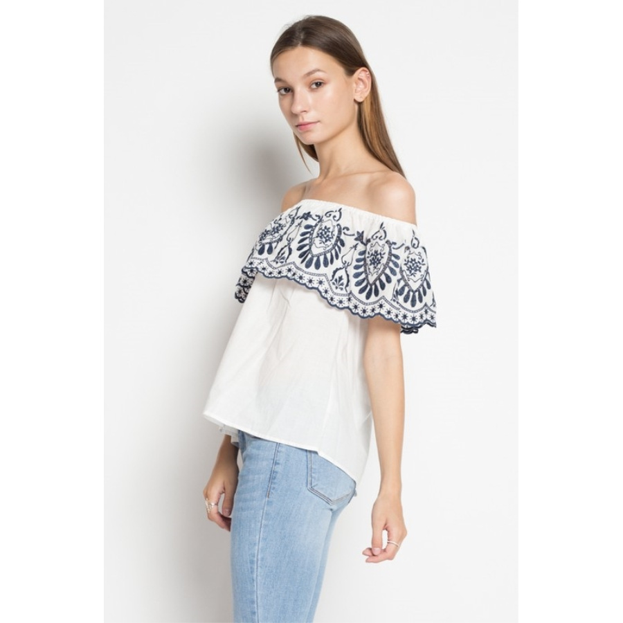 Blusa con diseño bordado cuello al hombro con vuelo.