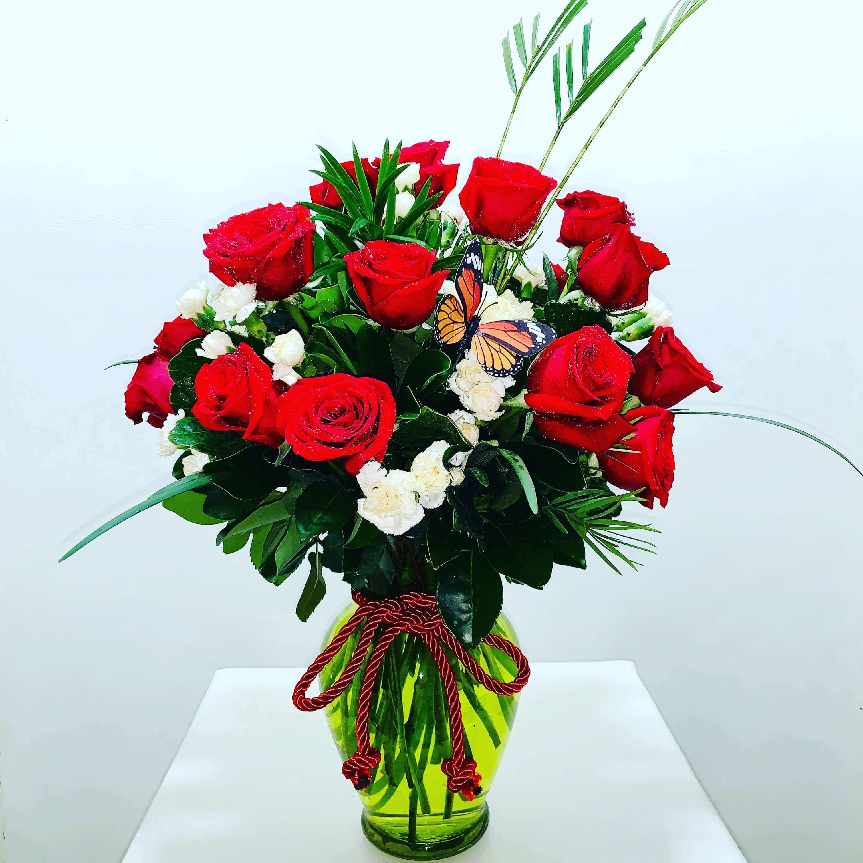 Arreglo de 24 rosas rojas en jarrón de cristal