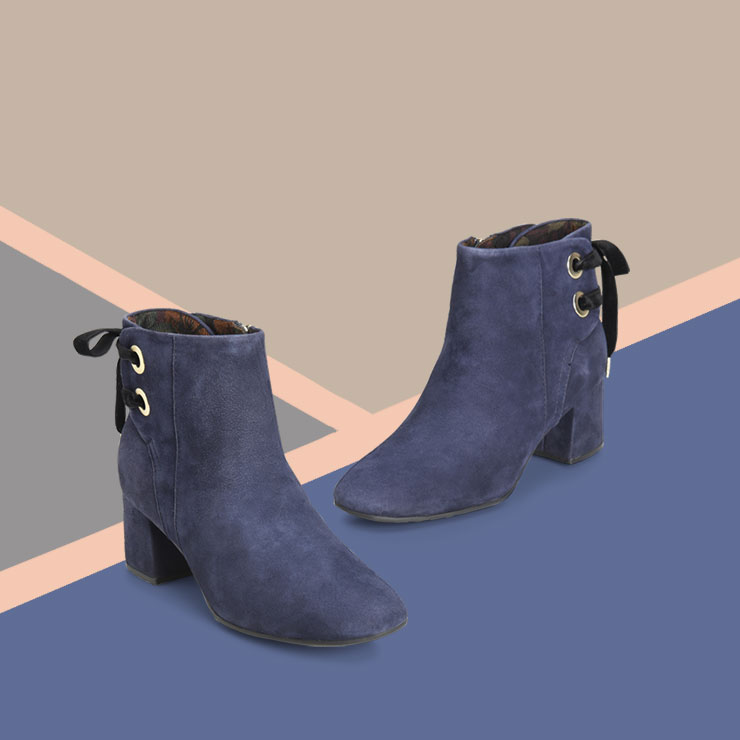 Navy suede Lloy bootie on a geometric background