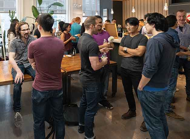Room full of people chatting at an Operation Code meetup in New York City.