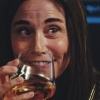 an image of Admiral Cornwell (Jayne Brook) grinning behind her whisky glass