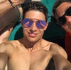 A selfie of Esteban Ocon topless and wearing sunglasses.
