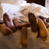 Four people's feet poking out from under the sheets at the end of a bed.