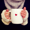 person holding coffee cup with a heart on it