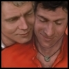 Starsky smiling, in his red longjohns and Chinese lucky coin necklace, looking down. Hutch is spooning him from behind, resting his chin on Starsky's shoulder, cheeks touching, and with a contented smile.