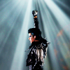 Adam Lambert in a spiky black jacket, one arm raised with microphone in hand, spotlight shining down on him