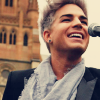 Blond Adam Lambert in a dark jacket, with a light gray scarf around his neck and a microphone standing in front of him