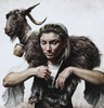 Woman holding black goat on shoulders