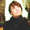 Amanda Tapping pulling a silly amused face and looking upward, hair in a ponytail with a leather jacket on in a brightly lit cave set