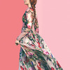Sophie Turner shown from the side, wearing a flowing dress with a large flower print, hair in a long braid