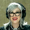 Moira Rose wearing headphones in a recording booth
