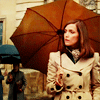 Moira MacTaggart, pensive in a trench & umbrella