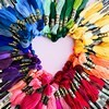 A heart shaped by skeins of embroidering yarn in rainbow colours