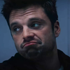 Oliver Queen from the TV series Arrow looking sternly beyond the viewer. He has cuts and bruises on his forehead and neck and is wearing a plain white t-shirt, the kind that is worn by hospital patients.