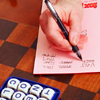 a hand writing down words in front of a Boggle word game